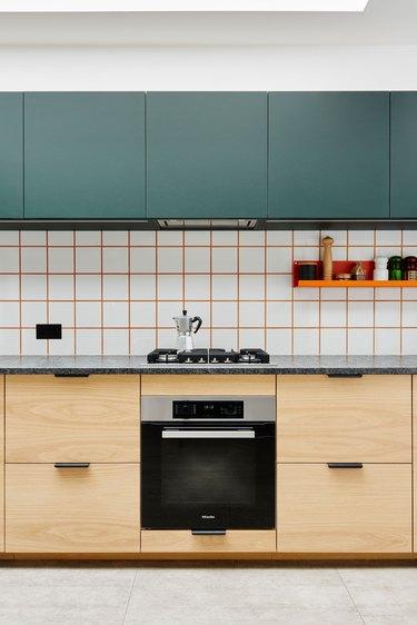 white tile kitchen backsplash with orange grout with green upper cabinets
