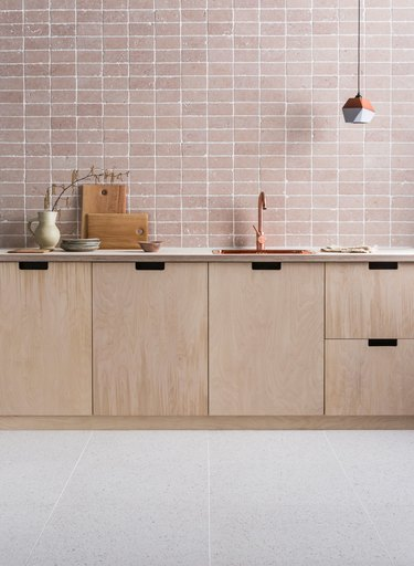 modern kitchen backsplash idea with dusty pink tumbled marble tile paired with plywood cabinets