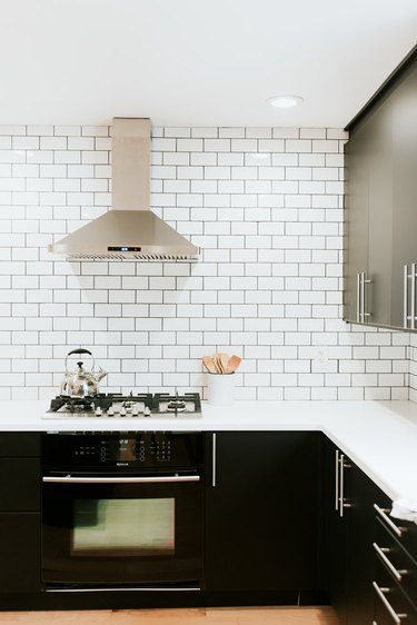 classic white subway tile kitchen backsplash with dark cabinetry