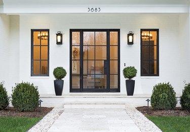 modern exterior door on white house with black steel frame