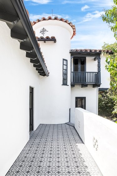 white traditional stucco homes with patterned tile walkway and balcony