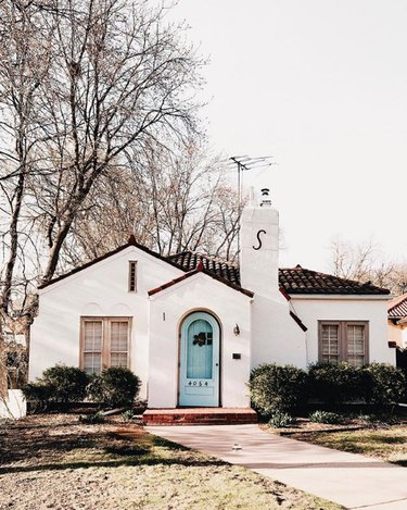 white traditional stucco homes with bright blue door and Spanish roof