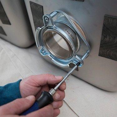 Installing a garbage disposal bracket.