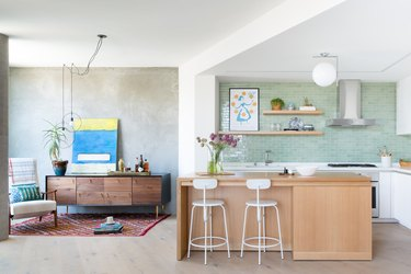 full-height sage green kitchen backsplash with white cabinets and wood island