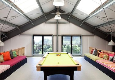 attic game room with lime green pool table, multi colored sectional sofas withe throw pillows, arched ceiling with metal beams.