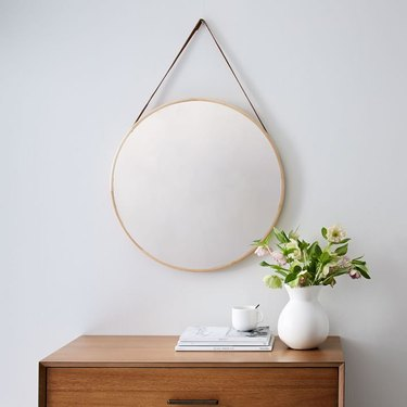 Tan-bordered round mirror with leather hanging strap