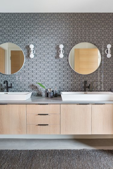 Midcentury modern style bathroom with patterned tile accent wall and floating vanity cabinet