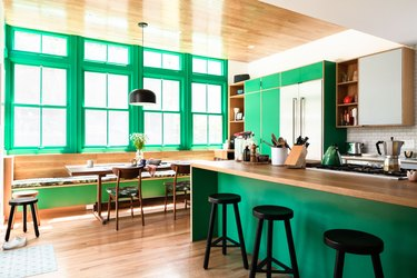 kelly green kitchen with large windows and walls painted in cool colors