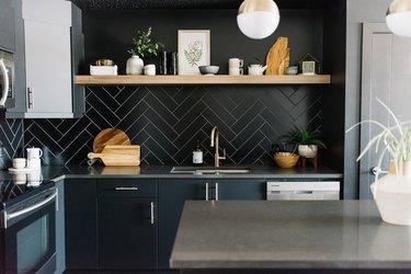 black kitchen backsplash with black cabinetry and open shelving