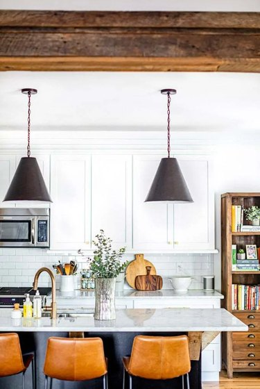 Industrial farmhouse kitchen with black pendant lights and reclaimed wood beams