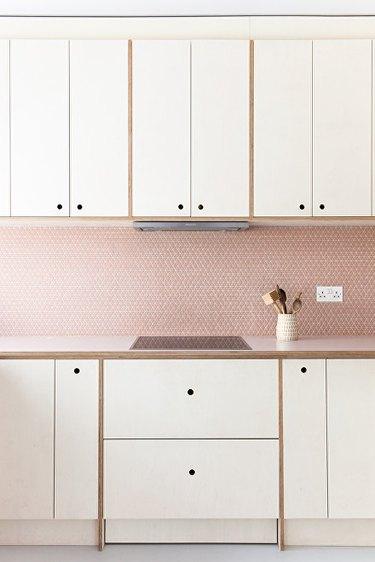 white kitchen cabinetry with pink mosaic kitchen backsplash