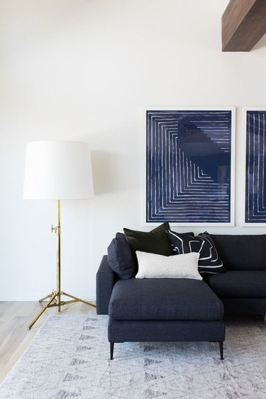navy blue living room idea designed by Studio Mcgee with blue sofa and artwork