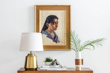 Leather handled vase sits atop a bedroom dresser