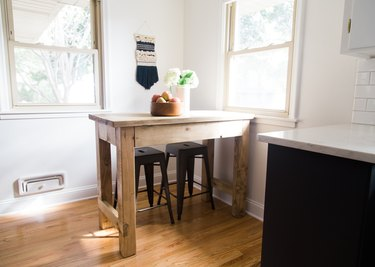 small kitchen table idea with rustic wood table and stools near windows