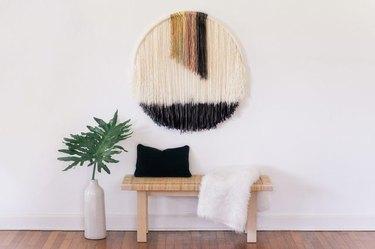 Dip-dye wall art hangs above an entryway bench