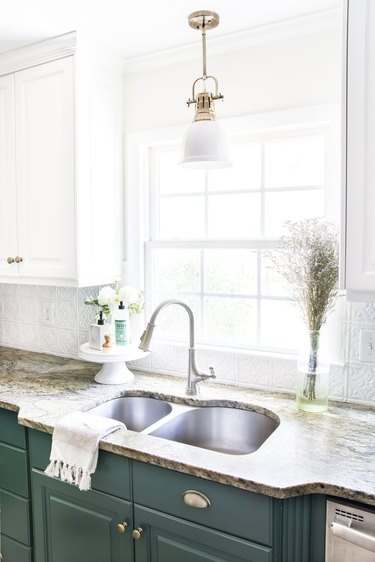 Budget kitchen lighting above sink with green lower cabinets and white upper cabinets