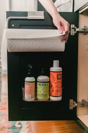 under sink storage with paper towel rack and clear caddy with cleaning supplies