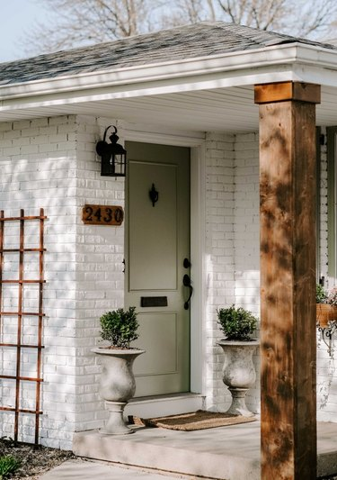white limewashed brick farmhouse exterior with green front door