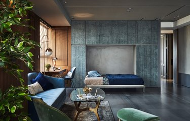 gray industrial color palette in living room with blue walled cabinets and murphy bed