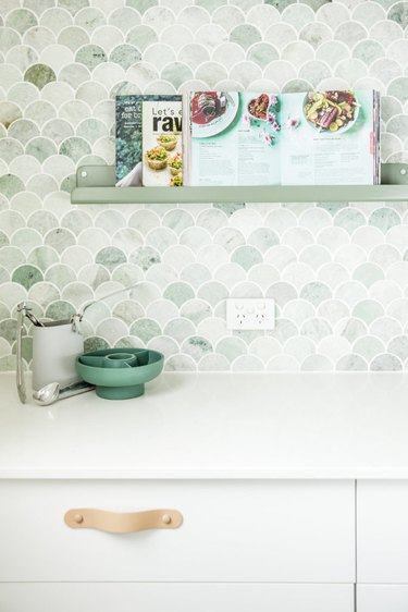 green kitchen backsplash with floating green shelf and white cabinets