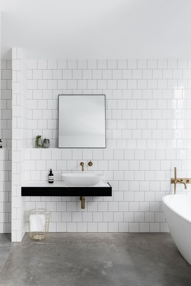Bathroom with bright white subway tile walls and dark concrete floor