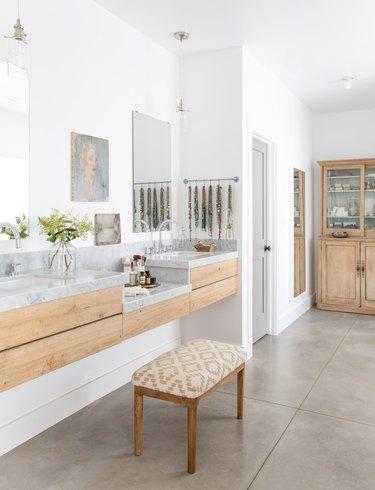 A vanity stool in a minimal bathroom with concrete floor