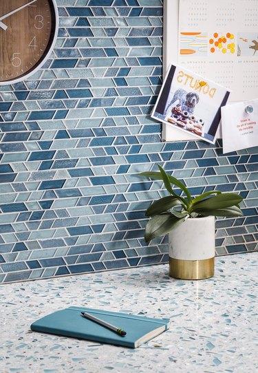 glass tile mosaic backsplash and terrazzo countertop in kitchen