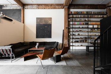 industrial pipe shelving in living room with gray sectional and leather chairs