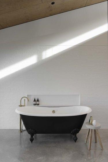 A black bathtub on concrete floors