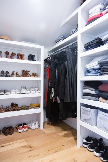 Attic Closet ideas with built-in shelving and light wood floors