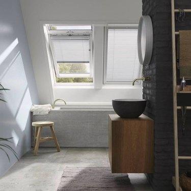 attic skylight designs in bathroom with black brick accent wall