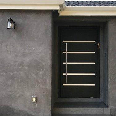 modern exterior door with black and long stainless door handle