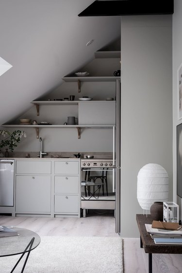 gray attic kitchen with open shelving and angled ceiling