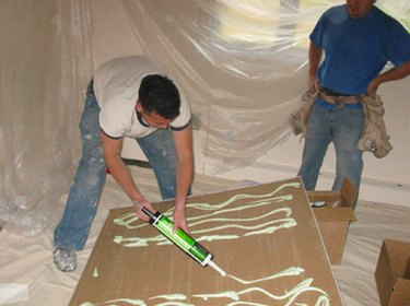 Spreading soundproofing glue.