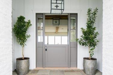 exterior door trim on gray front door with statement white wooden trim