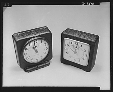 two wartime alarm clocks made of pressed wood and paper pulp