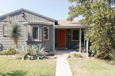 exterior door trim on gray clad house with orange door and wooden trim
