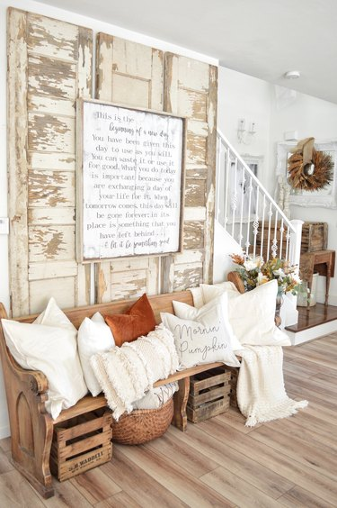 Rustic fall decor with chipped vintage doors and orange and white throw pillows
