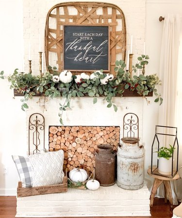 Rustic fall decor on fireplace mantle with tobacco basket and greenery