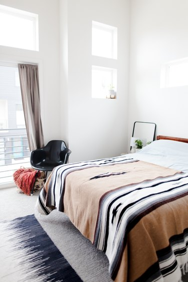 bedroom with area rug and accent chair and patterned throw on bed