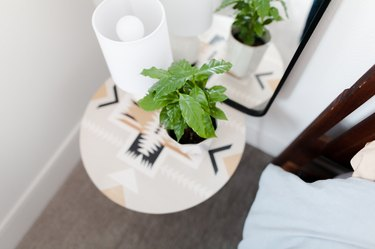 side table near with table lamp and plant near mirror