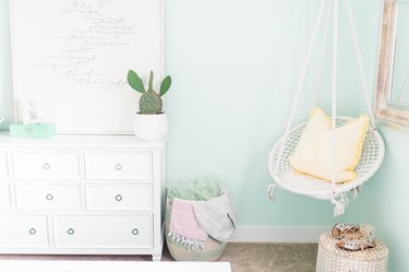 aqua color bedroom with white dresser and white hanging chair