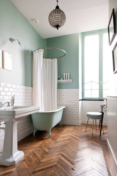 white and aqua color bathroom with herringbone wood floors and aqua claw foot tub