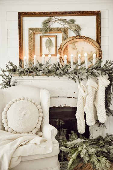 Rustic Christmas decorations on mantle with candles and winter greens