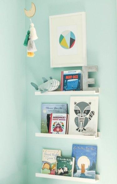 aqua color nursery with bookshelves