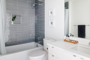 shower with gray wall tile in bathroom with white countertop