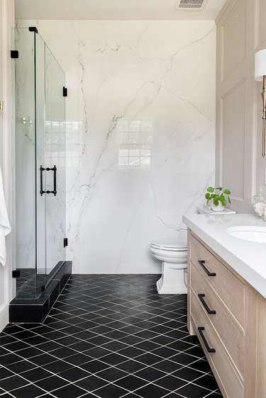 ivory color idea in bathroom with marble wall and black floor tile