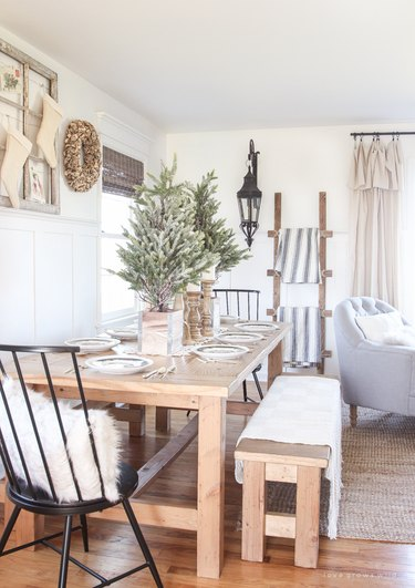 Rustic Christmas decorations in dining room with wood furniture and pine trees