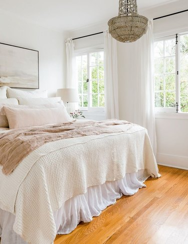 ivory color idea in master bedroom with crystal chandelier and pastel linens