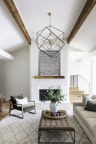 ivory color idea in sitting room with painted fireplace and modern light fixture